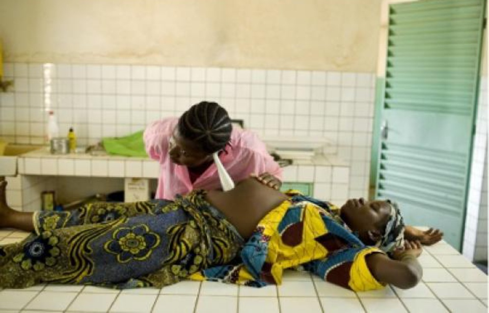 A midwife examines a 17-year-old girl during the early hours of labor. Photo: A. Kari
