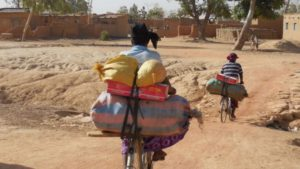 Bikes as the only possible mode of transportation. Two Zongo women carry their small businesses' goods