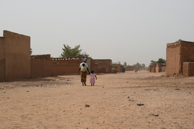 A mother with her two daughters, one on her back and the other holding her hand, walking down a road in Rimkieta